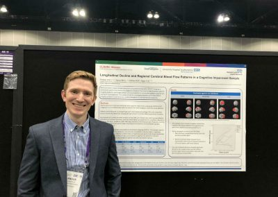 Dr Angus Prosser with his poster on longitudinal decline in brain blood flow patterns in dementia